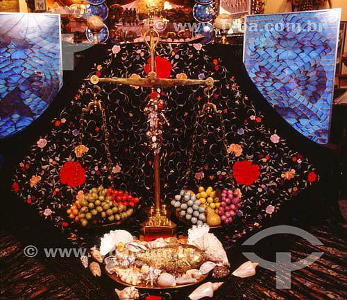 Cenário decorativo alusivo à oferenda religiosa utilizando bandejas feitas com asa de borboleta, cruz, concha e peixe