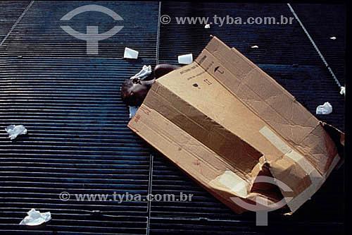 Menino de rua dormindo usando papelão como cobertor - Rio de Janeiro - RJ - Brasil  - Rio de Janeiro - Rio de Janeiro - Brasil