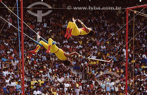 Trapezistas de circo com platéia ao fundo