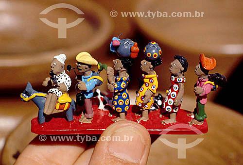 Mão segurando artesanato em barro com figuras de retirantes nordestinos