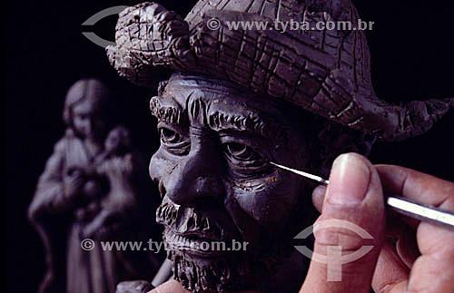 Artesanato em barro - detalhe de mão dando o acabamento na escultura