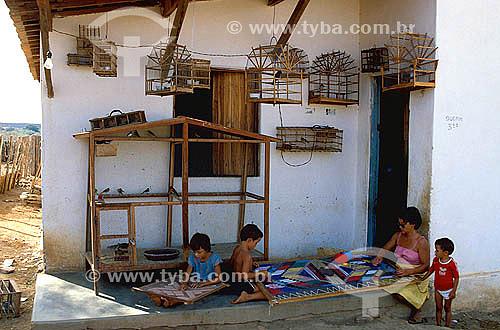 Artesanato em tecido - Mãe com filhos fazendo bordado - Casa com várias gaiolas de passarinho na parede  - Jaguari - Ceará - Brasil