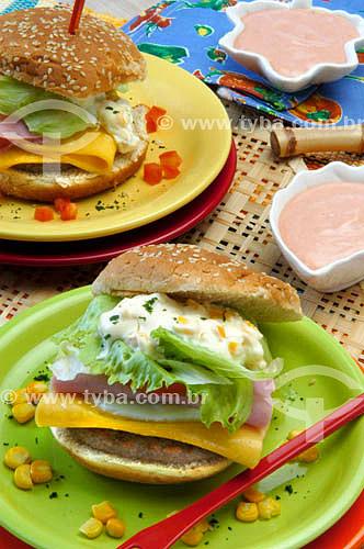 Culinária - sanduíches com queijo, presunto, ovo, alface e carne de hamburguer, acompanhados de molho rosé.