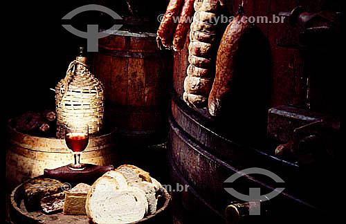 Adega com taça de vinho tinto, pães e frios.
