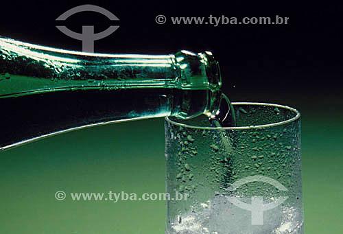 Bebida - água (close da garrafa e do copo de vidro)