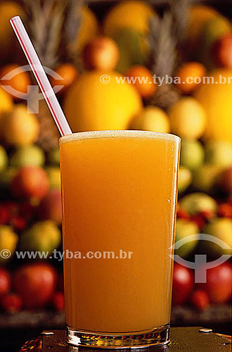 Copo de suco de laranja com canudo em primeiro plano e frutas ao fundo
