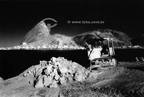 Trator trabalhando - Pão de Açúcar   ao fundo - Rio de Janeiro - RJ - Brasil  é comum chamarmos de Pão de Açúcar o conjunto da formação rochosa que inclui o Morro da Urca e o próprio Morro do Pão de Açúcar (o mais alto dos dois). O conjunto rochoso é Patrimônio Histórico Nacional desde 08-08-1973.  - Rio de Janeiro - Rio de Janeiro - Brasil