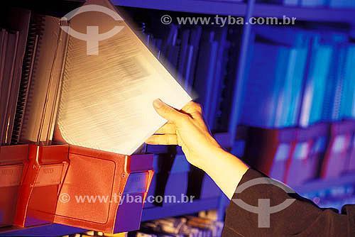 Mãos de uma executiva pegando documento em arquivo