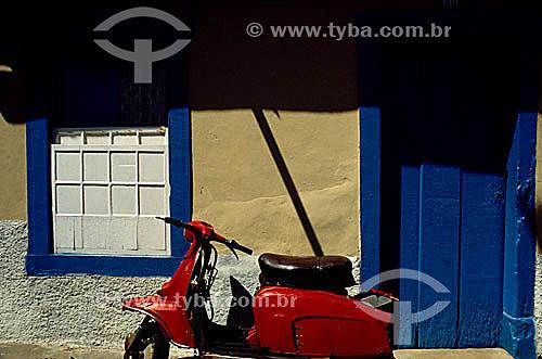 Motocicleta vermelha (vespa) em frente à uma casa de estilo colonial