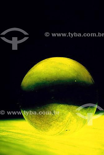 Efeito visual: esfera de vidro com luz amarela refletida