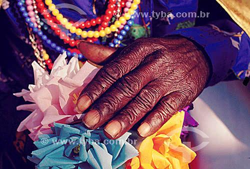 Detalhe de uma mão negra com flores e colares coloridos