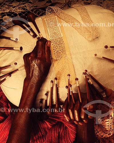 Artesanato: detalhe de mão negra tecendo renda de bilro