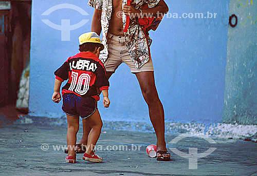 Homem e menino (com a blusa do Flamengo) brincando de jogar futebol com um copo de refrigerante - Brasil