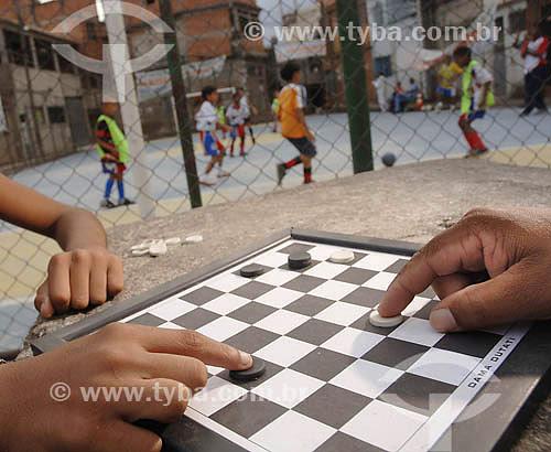 Jogo de Damas no Complexo do Alemão com quadra para futebol ao fundo - Rio de Janeiro - RJ - Brasil - Maio de 2006  - Rio de Janeiro - Rio de Janeiro - Brasil