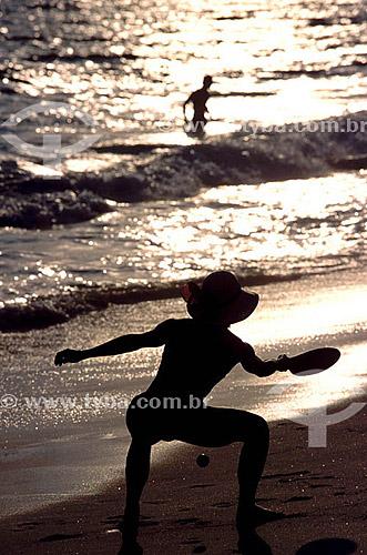 Lazer - silhueta de mulher jogando Frescobol na praia