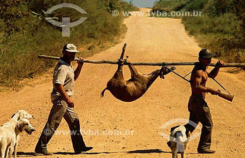 Homens atravessando a Transpantaneira com um veado abatido e dois cachorros - PARNA Pantanal Matogrossense - MT - Brasil  A área é Patrimônio Mundial pela UNESCO desde 2000.  - Mato Grosso - Brasil