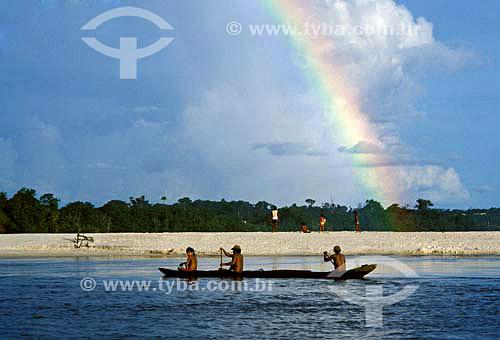 Índios cruzando Rio Negro em pequeno barco com arco-íris ao fundo - AM - Brasil / Data: 2010