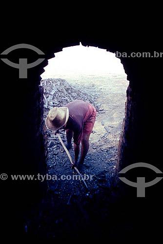 Habitante da Amazônia - Carvoeiro trabalhando o carvão vegetal com uma pá - forno artesanal - AM - Brasil  - Amazonas - Brasil