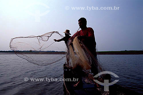 Pescadores na canoa jogando a rede de pescar no Lago Mamirauá - AM - Brasil  - Tefé - Amazonas - Brasil