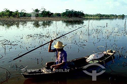 Pescador na canoa usando uma lança para pescar o Pirarucu (Arapaima gigas) - Rio Japurá - AM - Brasil / Data: 2008