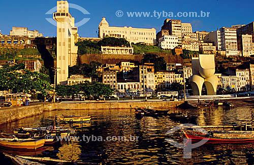 Vista do centro histórico de Salvador   com barcos em primeiro plano, o Elevador Lacerda ao fundo e a escultura