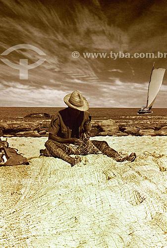 Pescador de chapéu concertando rede de pesca com saveiro no mar ao fundo - Salvador - BA - Brasil  - Salvador - Bahia - Brasil