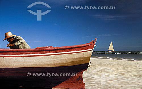 Pescador cuidando do barco e saveiro ao fundo na Praia de Itapoa - Salvador - Bahia - Brasil  - Salvador - Bahia - Brasil
