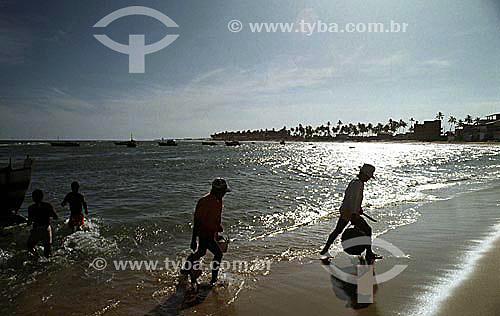 Silhueta de pescadores na praia de Itapoa iluminada pelo  pelo reflexo prateado dopôr-do-sol na água, com barcos e coqueiros ao fundo - Salvador - Bahia - Brasil  - Salvador - Bahia - Brasil