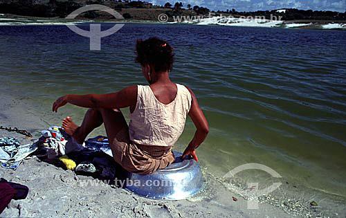Mulher sentada lavando roupa com a ajuda dos pés na  Lagoa de Abaeté - Salvador - Bahia - Brasil  - Salvador - Bahia - Brasil