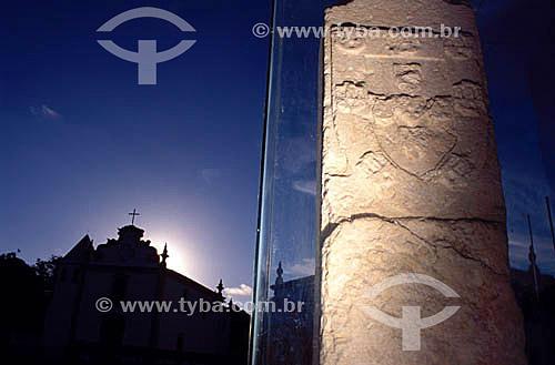 Marco Padrão ou Marco do Descobrimento (1503), com brasão da coroa de Portugal esculpida em pedra e a silhueta da Igreja Nossa Senhora da Pena (1535) ao fundo - Centro Histórico de Porto Seguro  - Litoral sul da Bahia - Brasil  A área denominada Costa do Descobrimento (Reserva da Mata Atlântica) é Patrimônio Mundial pela UNESCO desde 01-12-1999 e nela estão localizadas 23 áreas de proteção ambiental na Bahia (incluindo Porto Seguro).  - Porto Seguro - Bahia - Brasil