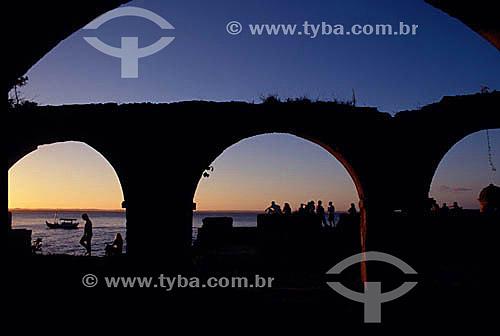 Silhueta de pessoas atrás das ruínas do Forte ao pôr-do-sol - Morro de São Paulo - Costa do Dendê - litoral sul da Bahia  - Cairu - Bahia - Brasil
