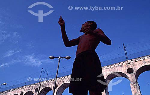 Menino empinando pipa em frente aos Arcos da Lapa - Centro do Rio de Janeiro - RJ - Brasil  Aqueduto em estilo romano do século XVIII (Rio colonial), com uma dupla arcada de 42 arcos. Patrimônio Histórico Nacional desde 05-04-1938.  - Rio de Janeiro - Rio de Janeiro - Brasil