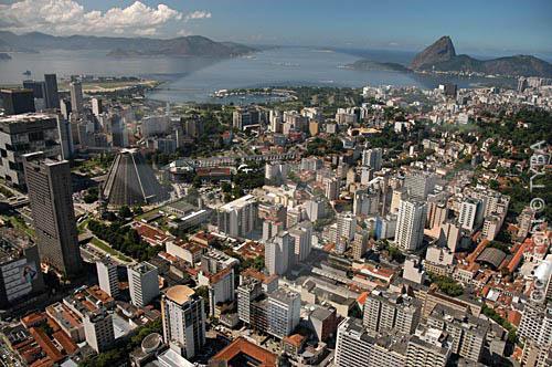 Vista aérea do Centro do Rio de Janeiro mostrando a  Catedral de São Sebastião do Rio de Janeiro (também conhecida como Catedral Metropolitana do Rio de Janeiro), os prédios da Petrobrás e do BNDES à esquerda, os Arcos da Lapa (1) ao centro e a Marina da Glória e o o Pão de Açúcar (2) ao fundo - Rio de Janeiro - RJ - Brasil (1) Aqueduto em estilo romano do século XVIII (Rio colonial), com uma dupla arcada de 42 arcos. Patrimônio Histórico Nacional desde 05-04-1938. (2) é comum chamarmos de Pão de Açúcar, o conjunto da formação rochosa que inclui o Morro da Urca e o próprio Morro do Pão de Açúcar (o mais alto dos dois). Nesta foto, o pequeno Morro Cara de Cão onde foi construído o Forte São João em 1578, é visto à direita como a parte mais baixa  e avançada sobre a Baía do mesmo complexo. O conjunto rochoso é Patrimônio Histórico Nacional desde 08-08-1973.  foto digitalData: 2005