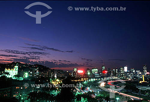Vista do Aterro do Flamengo ou Parque do Flamengo (1) no crepúsculo, com suas avenidas, o Outeiro da Glória (Igreja de Nossa Senhora da Glória do Outeiro) (2) no alto à esquerda, o Monumento aos Mortos da Segunda Guerra Mundial - Monumento aos Pracinhas - à direita e os prédios iluminados da Praia do Flamengo e do centro da cidade do Rio de Janeiro - RJ - Brasil (1) Mais conhecido como Aterro do Flamengo, o Parque Brigadeiro Eduardo Gomes é a mais extensa área de lazer da cidade. Construído sobre aterramento de 1,2 milhão de metros quadrados tomados ao mar, abrange uma faixa de terra que se estende do Aeroporto Santos Dumont até o Morro da Viúva, em Botafogo. O projeto, inaugurado em 1964, foi coordenado por Maria Carlota (Lota) Macedo Soares e os projetos arquitetônico e paisagístico são respectivamente de Affonso Eduardo Reidy e Burle Marx.  É Patrimônio Histórico Nacional desde 28-07-1965.(2) De forma poligonal, foi construída em estilo barroco brasileiro entre 1717 e 1739 e tem no seu inteior painéis recobertos por azulejos portugueses atribuídos ao mestre ceramista Valentim de Almeida. Ao lado encontra-se o Museu Imperial da Irmandade de Nossa Senhora da Glória do Outeiro. A igreja é Patrimônio Histórico Nacional desde 04-05-1938.  - Rio de Janeiro - Rio de Janeiro - Brasil