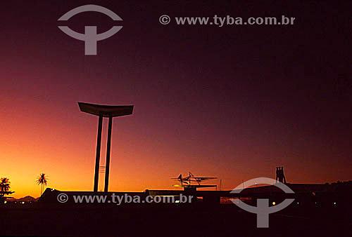 Silhueta do Monumento aos Mortos da Segunda Guerra Mundial - Monumento aos Pracinhas - construído entre 1957 e 1960 - Aterro do Flamengo ou Parque do Flamengo   ao pôr-do-sol - Rio de Janeiro - RJ - Brasil  Mais conhecido como Aterro do Flamengo, o Parque Brigadeiro Eduardo Gomes é a mais extensa área de lazer da cidade. Construído sobre aterramento de 1,2 milhão de metros quadrados tomados ao mar, abrange uma faixa de terra que se estende do Aeroporto Santos Dumont até o Morro da Viúva, em Botafogo. O projeto, inaugurado em 1964 e tombado em 1965, foi coordenado por Maria Carlota (Lota) Macedo Soares e os projetos arquitetônico e paisagístico são respectivamente de Affonso Eduardo Reidy e Burle Marx.  é Patrimônio Histórico Nacional desde 28-07-1965.  - Rio de Janeiro - Rio de Janeiro - Brasil