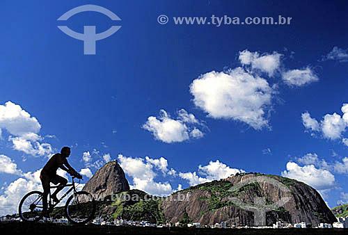 Ciclista com Pão de Açúcar   ao fundo - Rio de Janeiro - RJ - Brasil / Data: 2002  é comum chamarmos de Pão de Açúcar, o conjunto da formação rochosa que inclui o Morro da Urca e o próprio Morro do Pão de Açúcar (o mais alto dos dois). O conjunto rochoso é Patrimônio Histórico Nacional desde 08-08-1973.