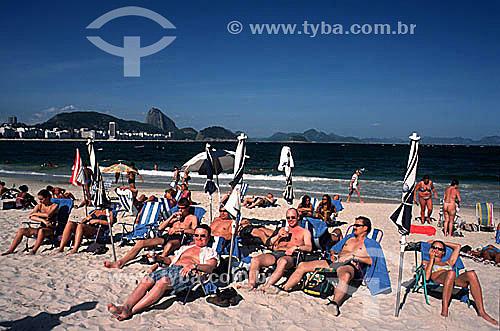 Turistas descansando na Praia de Copacabana com o Pão de Açúcar ao fundo - Rio de Janeiro - RJ - Brasil  - Rio de Janeiro - Rio de Janeiro - Brasil