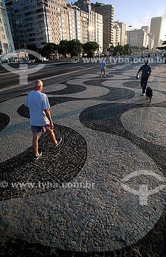 Pessoas caminhando no calçadão de Copacabana  pela manhã - Rio de Janeiro - RJ - Brasil / Data: 05/2002  A Avenida Atlântica foi inaugurada em 1906 com apenas uma pista. A forma atual data de 1970 e o projeto paisagístico é de Roberto Burle Marx, que manteve do calçadão antigo tanto as pedras portuguesas quanto o padrão gráfico de