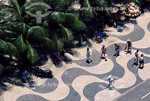 Calçadão de Copacabana com pessoas caminhando - Rio de Janeiro - RJ - Brasil  A Avenida Atlântica foi inaugurada em 1906 com apenas uma pista. A forma atual data de 1970 e o projeto paisagístico é de Roberto Burle Marx, que manteve do calçadão antigo tanto as pedras portuguesas quanto o padrão gráfico de