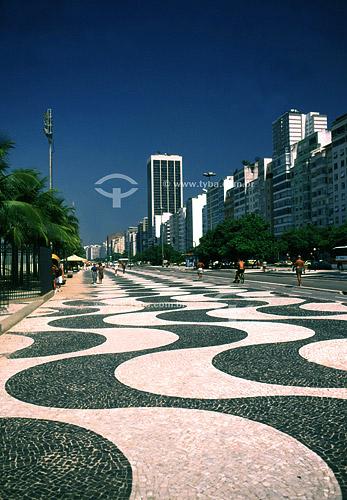 Vista do Calçadão de Copacabana com prédios ao fundo, Rio de Janeiro - RJ - Brasil  A Avenida Atlântica foi inaugurada em 1906 com apenas uma pista. A forma atual data de 1970 e o projeto paisagístico é de Roberto Burle Marx, que manteve do calçadão antigo tanto as pedras portuguesas quanto o padrão gráfico de
