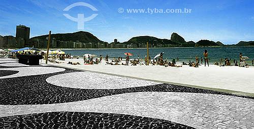 Calçadão de Copacabana com pessoas na praia - Rio de Janeiro - RJ - Brasil   A Avenida Atlântica foi inaugurada em 1906 com apenas uma pista. A forma atual data de 1970 e o projeto paisagístico é de Roberto Burle Marx, que manteve do calçadão antigo tanto as pedras portuguesas quanto o padrão gráfico de