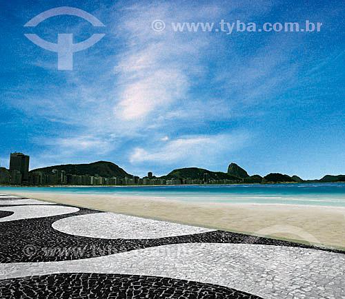 Detalhe do calçadão de Copacabana  em primeiro plano com a praia e o Pão de Açúcar ao fundo - Rio de Janeiro - RJ - Brasil  A Avenida Atlântica foi inaugurada em 1906 com apenas uma pista. A forma atual data de 1970 e o projeto paisagístico é de Roberto Burle Marx, que manteve do calçadão antigo tanto as pedras portuguesas quanto o padrão gráfico de