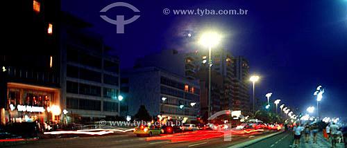Movimento ao cair da noite em Ipanema com pessoas caminhando no calçadão e as luzes dos carros nas pistas da Av. Vieira Souto à esquerda - Rio de Janeiro - RJ - Brasil  - Rio de Janeiro - Rio de Janeiro - Brasil