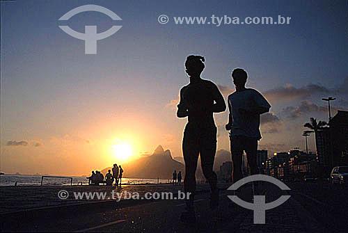 Silhueta de casal correndo na Praia de Ipanema ao pôr-do-sol com o Morro Dois Irmãos ao fundo - Rio de Janeiro - RJ - Brasil  - Rio de Janeiro - Rio de Janeiro - Brasil