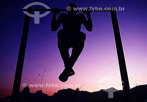 Silhueta de homem exercitando-se em barra na orla de Ipanema ao pôr-do-sol com o Morro Dois Irmãos e a Pedra da Gávea ao fundo à esquerda - Rio de Janeiro - RJ - Brasil  - Rio de Janeiro - Rio de Janeiro - Brasil