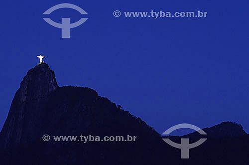 Silhueta do Cristo Redentor sobre o Morro do Corcovado iluminado ao cair da noite  - Rio de Janeiro - Rio de Janeiro - Brasil