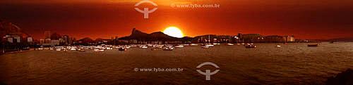 Vista panorâmica do Cristo Redentor ao pôr-do-sol com  barcos na Baía de Guanabara em primeiro plano - Rio de Janeiro - RJ - Brasil   - Rio de Janeiro - Rio de Janeiro - Brasil