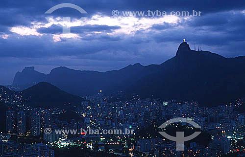 Vista aérea da cidade ao cair da noite com os prédios dos bairros de Botafogo e Flamengo em primeiro plano, o Cristo Redentor iluminado à direita e a Pedra da Gávea ao fundo à esquerda - Rio de Janeiro - RJ - Brasil  - Rio de Janeiro - Rio de Janeiro - Brasil