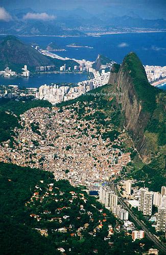 Vista do alto da Pedra da Gávea (1) mostrando em primeiro plano, parte do bairro de São Conrado, seguido da Rocinha (2) e do Morro dos Dois Irmãos (1). Mais atrás, a Lagoa Rodrigo de Freitas (3) - Rio de Janeiro - RJ - Brasil. Data: 2001(1) A Pedra da Gávea e o Morro Dois Irmãos são Patrimônios Históricos Nacionais desde 08-08-1973.(2) Em 1992, a Rocinha, considerada até então a maior favela do Rio de Janeiro com seus 120 mil habitantes foi oficializada bairro.(3) Patrimônio Histórico Nacional desde 19-06-2000.