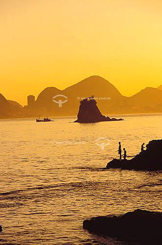 Silhuetas de pescadores e pedras na praia de Itapuca com o Rio de Janeiro ao fundo - Niterói - RJ - Brasil  - Niterói - Rio de Janeiro - Brasil